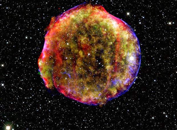 """Foto de los restos de la supernova de Tycho en rayos X, infrarrojo y visible. En 1572 apareció en la constelación de Casiopea una """"estrella nueva"""" que fue vista por Tycho Brahe y otros astrónomos de la época. Su estudio nos ayuda a entender el origen de este tipo de supernovas tan importantes en cosmología.- NASA"""